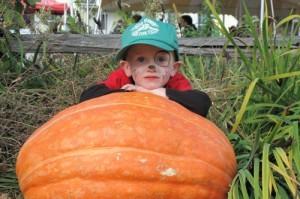 Cedar Circle Farm, boy with giant pumpkin by Karen Rogers3
